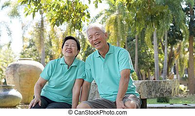 Asian senior couple relaxing in the park