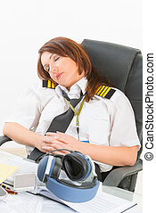 Woman airline pilot sleeping in the office - Overworked...
