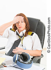 Tired woman airline pilot in the office - Overworked tired...