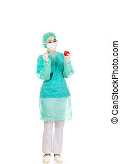 Young female cardiologist surgeron holding heart and scalpel...