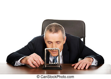 Businessman in office playing with newton balls - Mature...