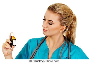 Female nurse or doctor holding medicine bottle in the hand