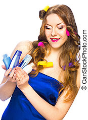 Beautiful woman with long hair in curlers holding products...