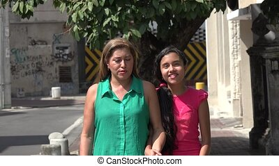 Mother and Daughter Walking on Urban Street