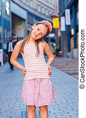Outdoor fashion portrait of a cute little girl of 7-8 years...