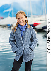 Outdoor portrait of a cute little girl wearing grey coat