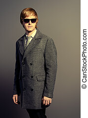classic suit - Elegant young man in a coat and sunglasses....