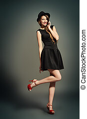 red shoes - Joyful pretty girl wearing black dress and black...