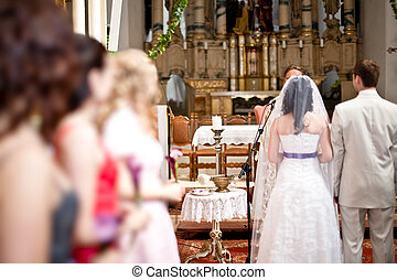 Bridesmaid standing in row during wedding ceremony holding...