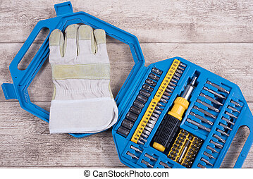 steel toolset and working glove on a wooden table and...