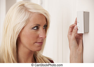Woman Adjusting Central Heating Thermostat