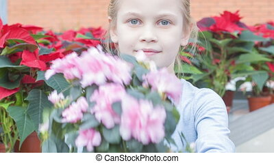 Little girl upholding a flower. - Kid and flower. Little...