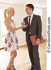 Estate Agent Handing Over Keys To Female House Buyer