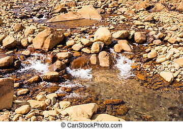Clear shallow water flowing and splashing on bare rocks -...