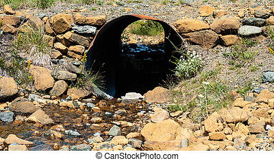 Looking through rusted corrugated metal pipe in rocky ground