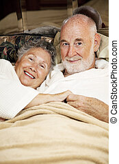 Sleepy Seniors - Happy senior couple snuggling in bed...