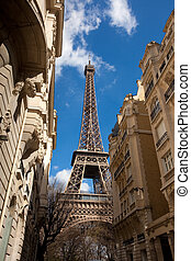 eiffel tower in street - view on eiffel tower emerging from...