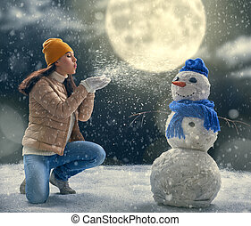 woman plaing with a snowman
