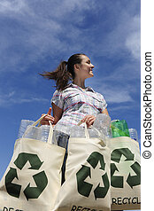 recycling: woman holding bag with plastic bottles against...