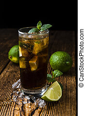 Cuba Libre longdrink with pieces of fresh lime and crushed...