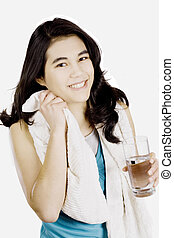 Tenage girl drinking water while wiping off sweat - Teenage...