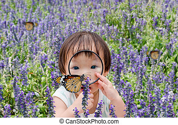 girl looking at butterfly with magnifying glass
