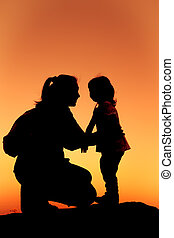 Silhouette of mother and daughter clasping hand together at sunset.