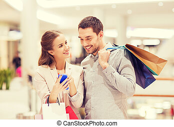 couple with smartphone and shopping bags in mall - sale,...