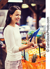 happy woman with basket and tablet pc in market - sale,...