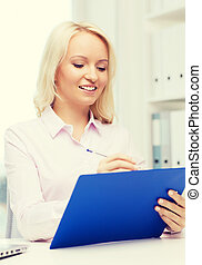 smiling businesswoman with clipboard in office - education,...