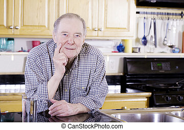 Elderly man leaning on counter