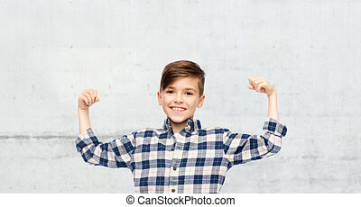 happy boy in checkered shirt showing strong fists -...