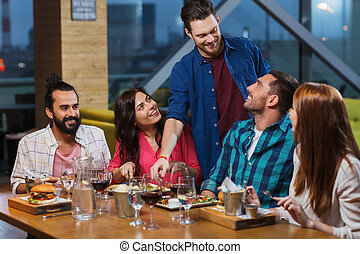 friends dining and drinking wine at restaurant - leisure,...