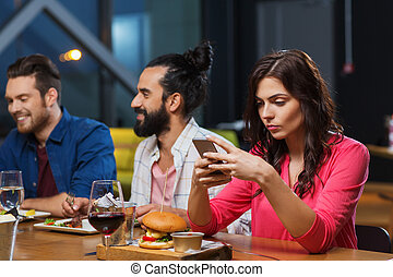 woman with smartphone and friends at restaurant - leisure,...