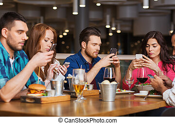 friends with smartphones dining at restaurant - leisure,...