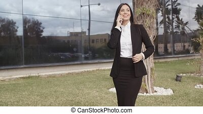 Elegant businesswoman chatting on her mobile phone as she...