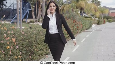 Busy young businesswoman walking along a street chatting on...