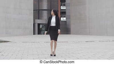 Young businesswoman walking towards the camera as she exits...