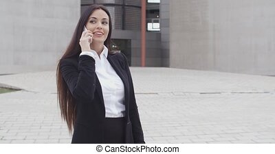 Attractive businesswoman checking her mobile phone for...