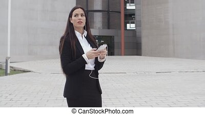 Young businesswoman talking on her mobile using an earplug...