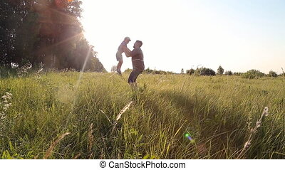 Young boy walking with his father in a grassy field ins...