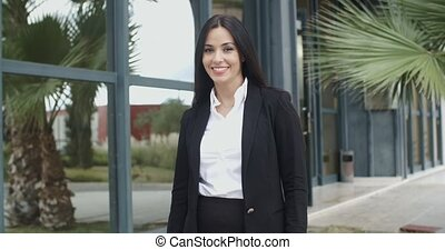Smiling friendly young businesswoman standing outside a...
