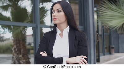 Confident serious young businesswoman standing with folded...