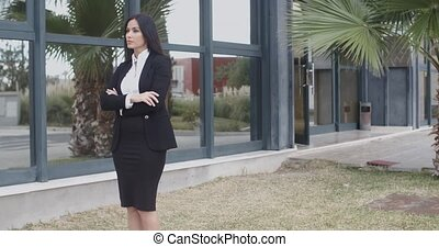 Confident serious young businesswoman standing waiting on...