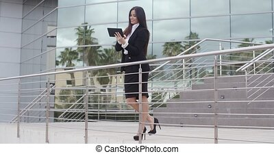 Elegant successful young businesswoman standing on the...