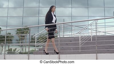 Stylish confident business manageress or executive walking...