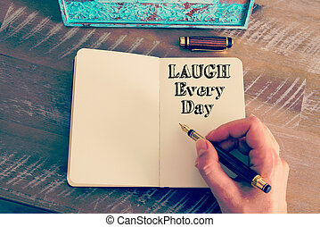 Motivational message LAUGH EVERY DAY written on notebook -...