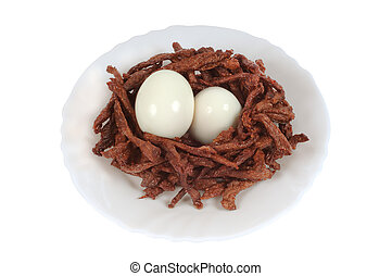 Meat sticks decorated in the form of bird nests with two boiled eggs. Isolated on white