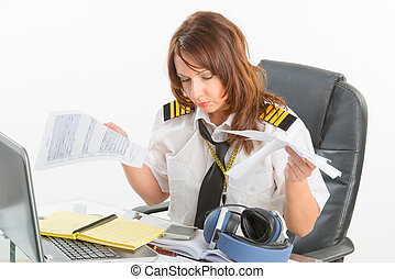 Overworked woman airline pilot in the office - Overworked...