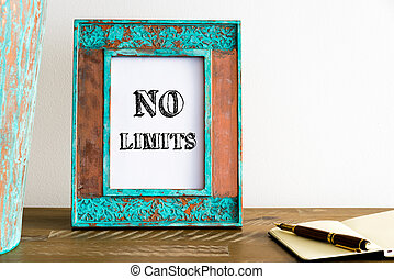 Vintage photo frame on wooden table with text NO LIMITS -...
